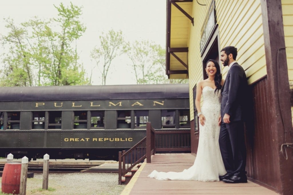 Bride and groom standing in front of a train at their Connecticut wedding