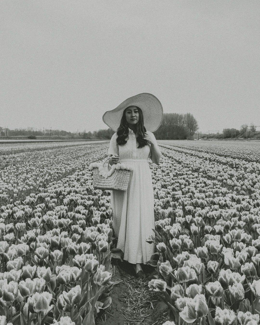 Woman wearing white dress in tulip fields in Holland