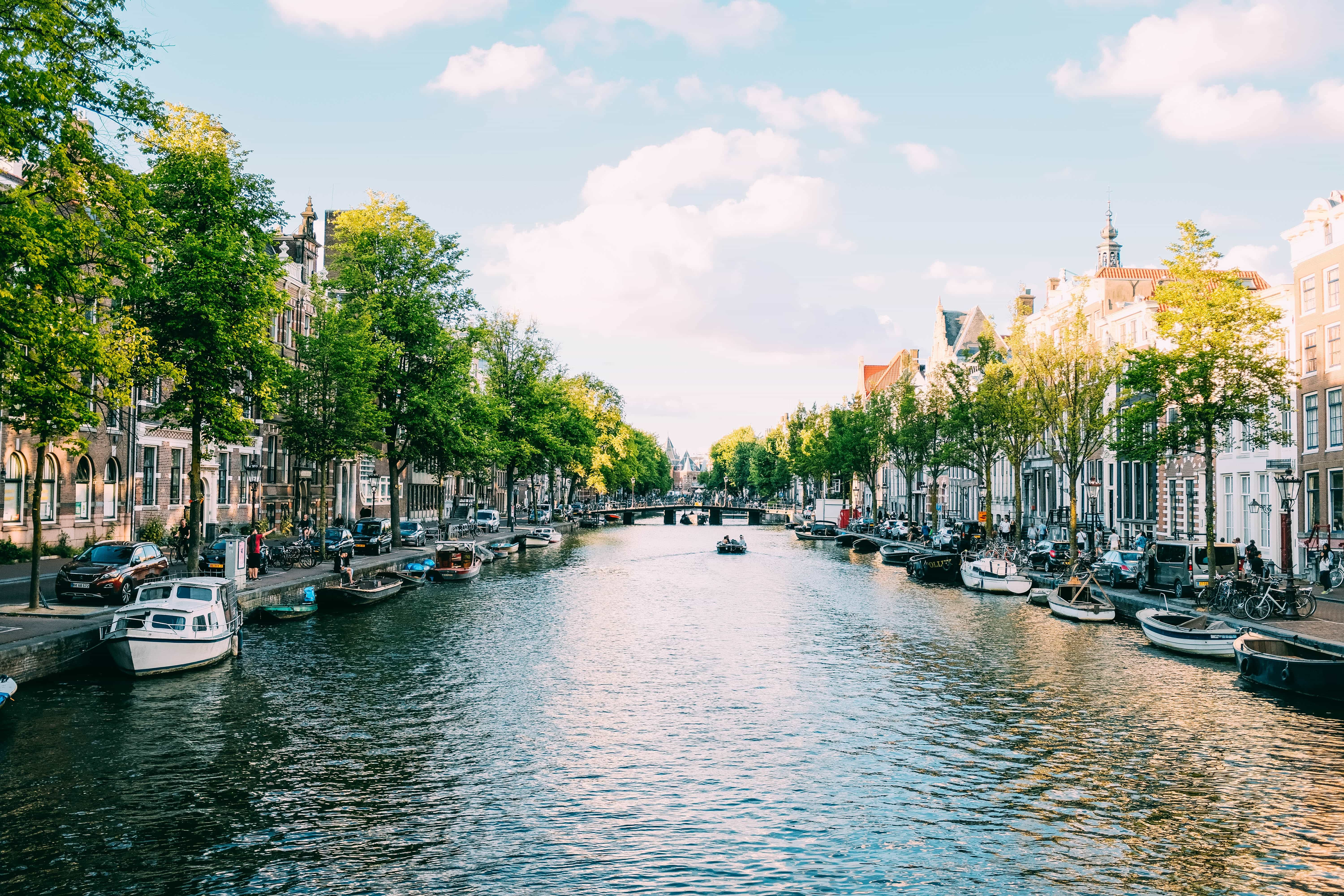 A picture of an Amsterdam canal, boats lining the edges and a bridge in the distance.