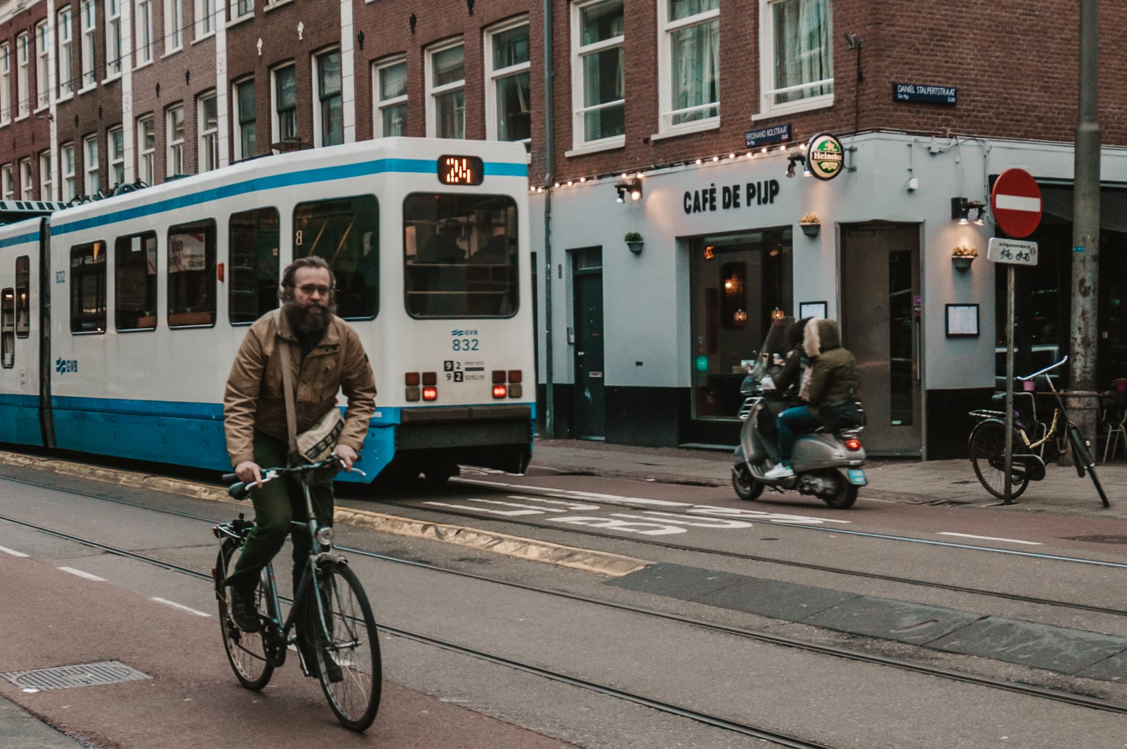 A man rides his bicycle on the bike path in Amsterdam, outside the cafe, Cafe De Pijp. A tram is passing behind him.