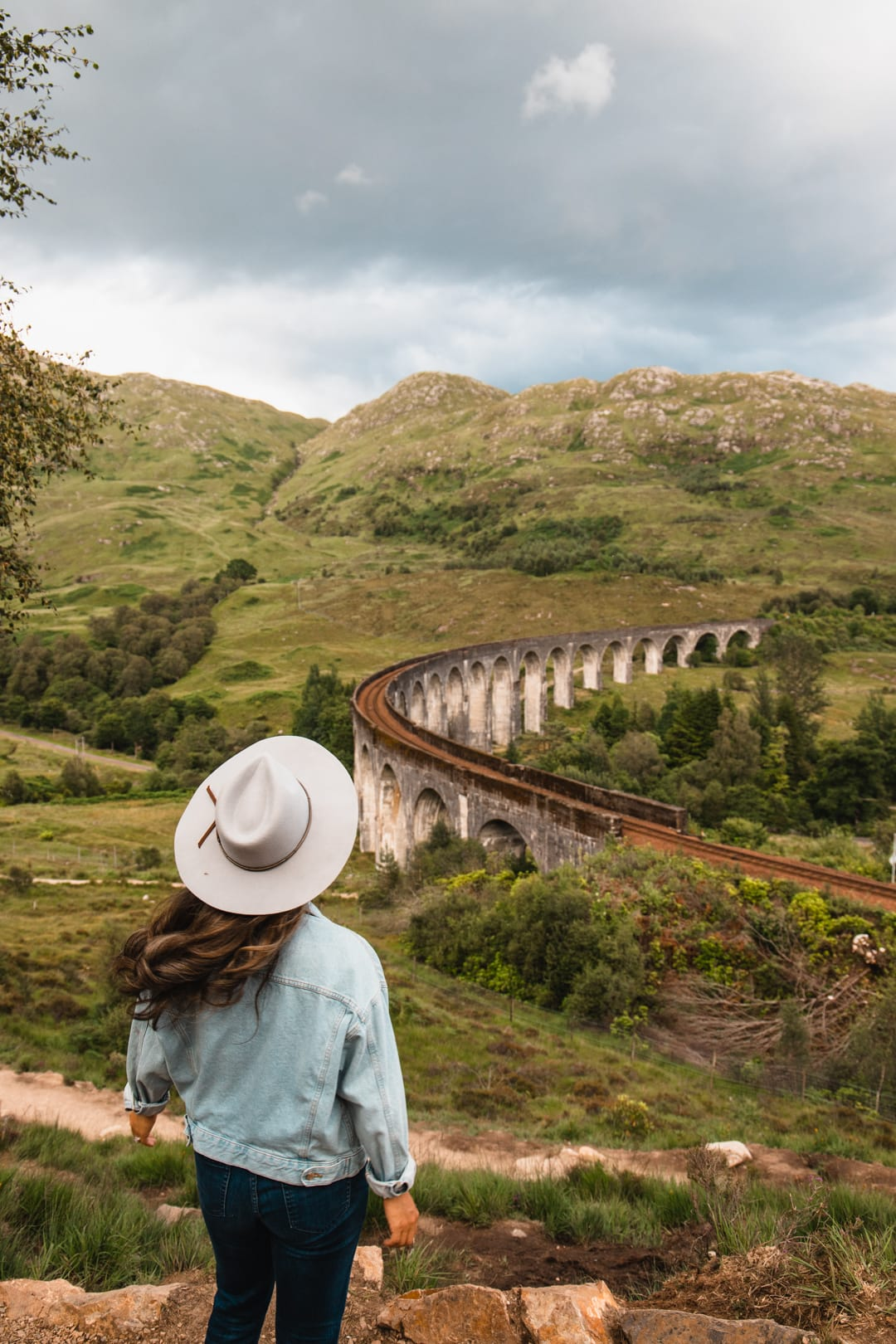 Girl looking at the Harry Potter bridge in Scotland, one of the most Instagrammable places in Scotland, best places for landscape photography in scotland