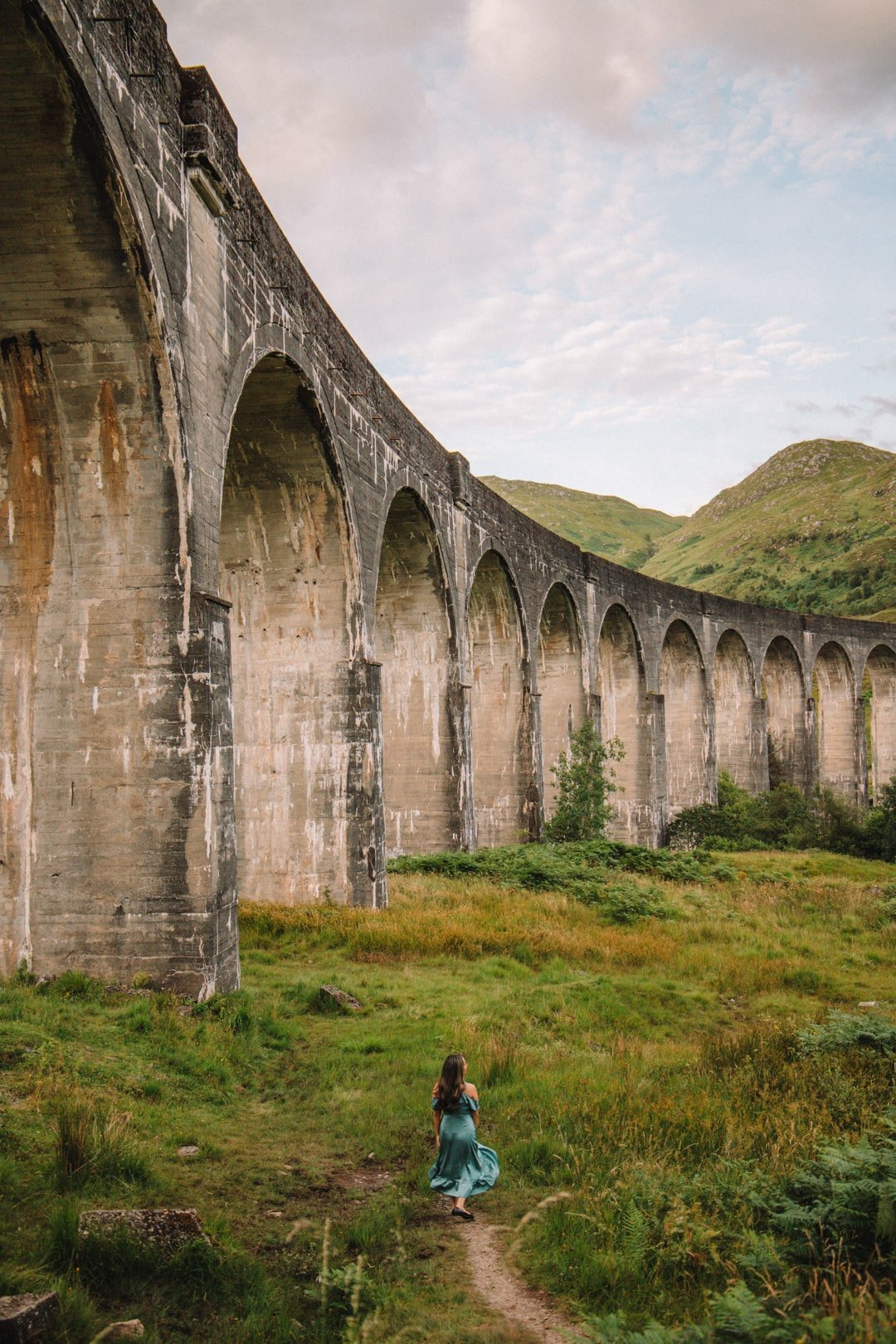 Girl at base of the Harry Potter bridge in Scotland, one of the most Instagrammable places in Scotland, best places for landscape photography in scotland