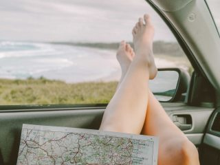 Girl holding a map in car rental in Aruba with view of ocean