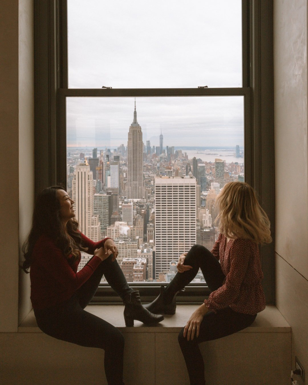 two girls looking out the window of rockefeller center - Girls Trip Ideas
