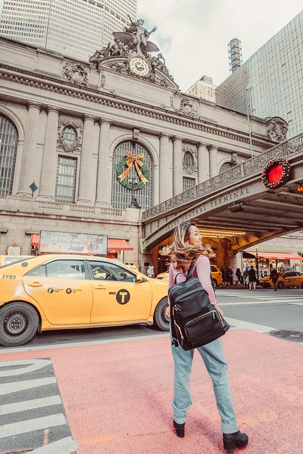 Woman taking an Instagram photo in front of Grand Central with a taxi