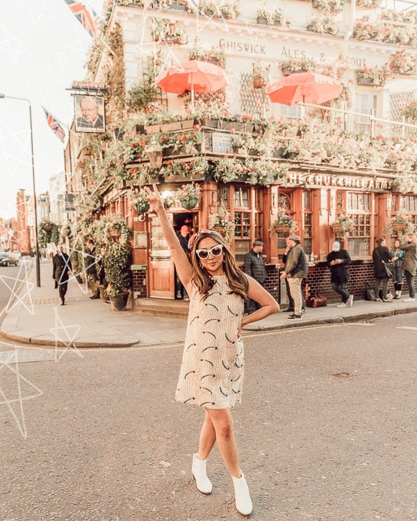woman standing in front of churchhill arms taking an instagram photo in front of the most instagrammable places in london