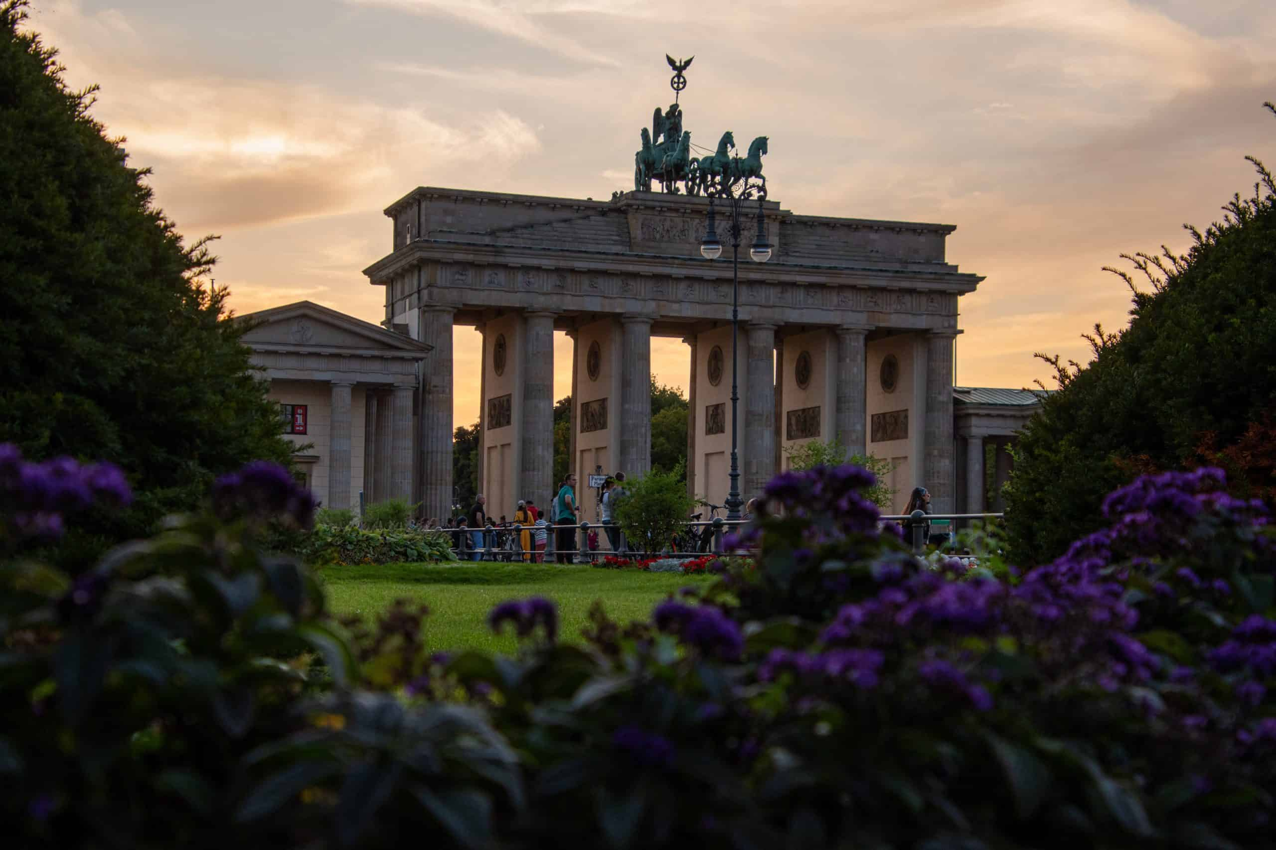 Photo is of Brandenburg Gate at sunset in front of some flower bushes. This is a great staycation Berlin place to visit because it isn't teeming with tourists.