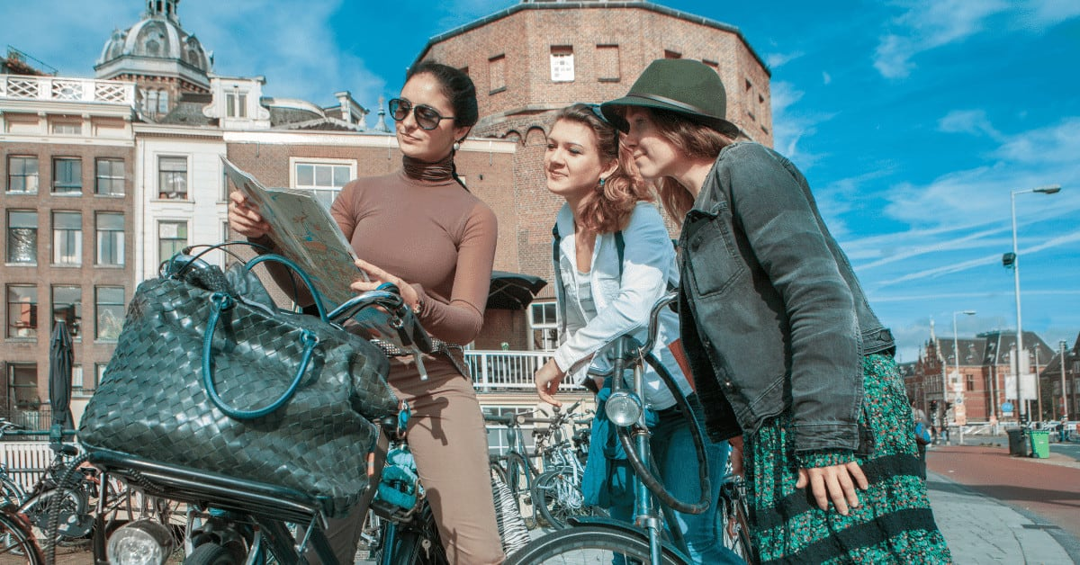 Three women looking at a map of Amsterdam to learn how to get around and brainstorm how to meet people in Amsterdam.