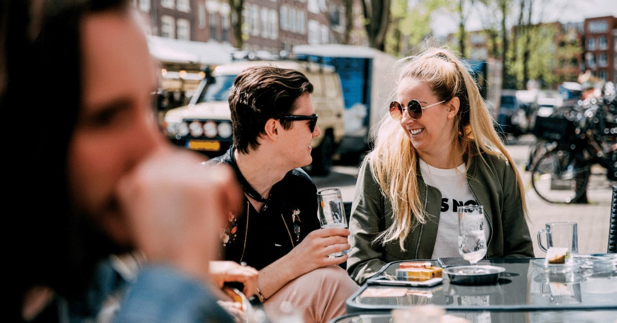 Couple enjoying beer at an outdoor pub talking about how learning Dutch is a great way to make friends in Amsterdam.